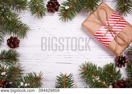 Christmas Greeting Card Concept. Gift Box With Christmas Tree And Decoration On White Wooden Backgro