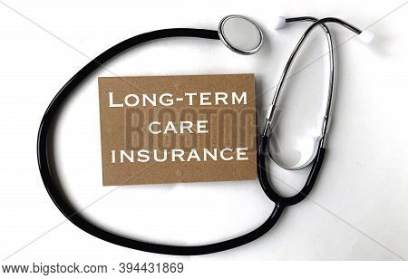 Long-term Care Insurance On Craft Paper.next To It Is A Stethoscope On A White Background.