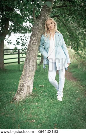 Blonde Woman Wearing Blue And White Leaning Against A Tree Outdoors