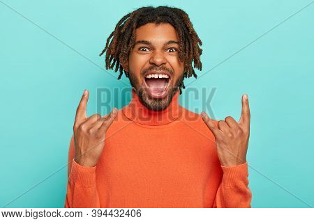 Energized Dark Skinned Young Man Rocks On Party, Brings Positive Vibes, Shows Rock N Roll Gesture, K