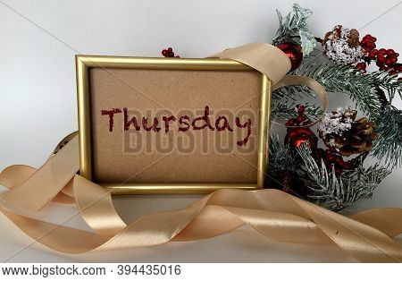 Thursday On Craft Paper In A Frame On A White Background.next To The Spruce Branches,berries ,ribbon