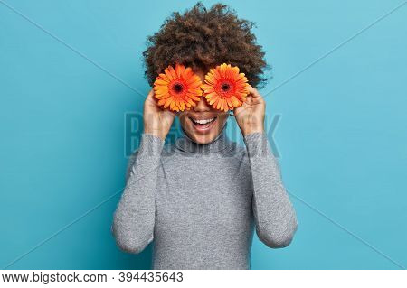 Playful Positive Curly Woman Covers Eyes With Two Orange Gerbera Daisy, Tells Womens Secrets, Has Ha