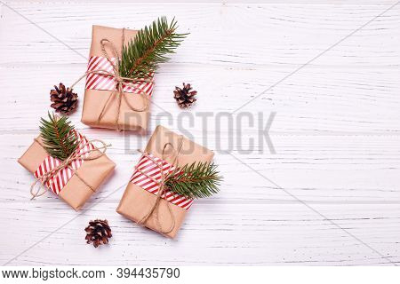 Christmas Greeting Card Concept. Gift Boxes Craft Paper With Christmas Tree Branch On White Wooden B