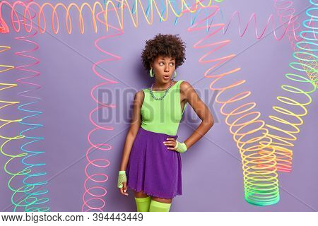 Surprised Dark Skinned Woman Keeps Hand On Waist, Looks Shocked Away, Wears Bright Shirt, Skirt And