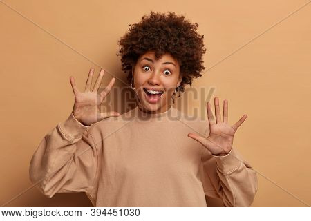 Funny Playful Young Woman With Curly Hairstyle, Pulls Palms Towards Camera, Laughs Happily, Has Joyo
