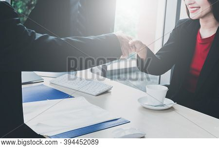 Shaking Hands Of Business People Between Man With Woman In The Office For Collaborative Teamwork. Bo