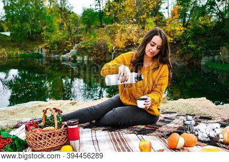 Girl Sitting On Colorful Plaid Having Autumn Picnic. Concept Of Warm Sunny Autumn Day, Picnic Outsid