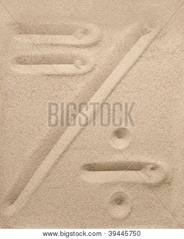 Division and an equal sign from sand
