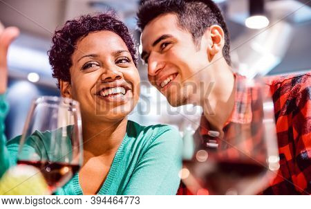 Happy Mixed Race Couple Of Lovers Drinking Red Wine At Fancy Winery Bar - Handsome Man Whispers Soft