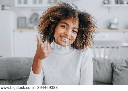 Happy Young Woman With Trendy Kinky Hairstyle And Dark Skin Smiles Showing Thumbs-up Against Modern
