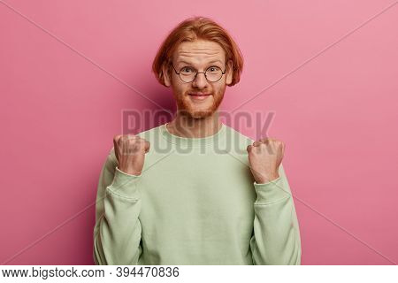 Studio Shot Of Relieved Ginger Caucasian Man Clenches Fists, Anticipates For Something Good Happened