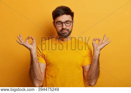People, Healthy Lifestyle And Yoga Concept. Relaxed Bearded Man Practices Peace On Mind, Keeps Finge