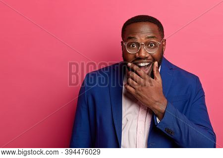 Joyful Black Man Boss Holds Chin And Laughs Happily, Dressed Formally, Has Pleased Funny Expression,