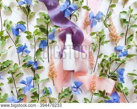 Mockup Of Unbranded White Plastic Spray Bottle, Blue And Pink Flowers And Silk Ribbons On White Tabl
