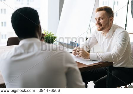 Smiling Businessman Listening To African American Business Partner Talking About New Project Sitting