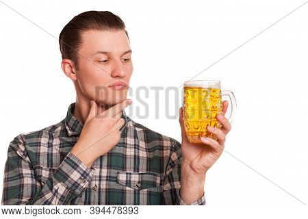 Young Handsome Man Looking At The Glass Of Beer In His Hand With Doubt, Isolated On White. Attractiv