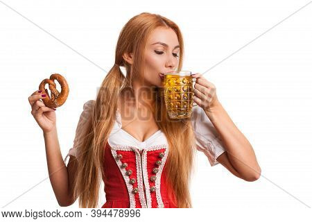 Portrait Of A Gorgeous Sexy Bavarian Girl Sipping Delicious Beer From A Mug, Holding Pretzel, Isolat
