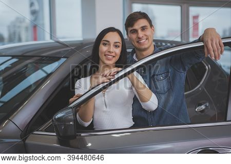 Young Handsome Man And His Cheerful Beautiful Girlfriend Posing Near Their New Automobile At The Dea