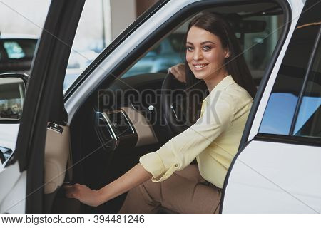 Excited Young Woman Smiling To The Camera, Getting In A New Automobile At The Dealership. Cheerful B
