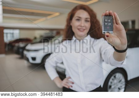 Selective Focus On Car Key In The Hand Of Cheerful Woman At The Dealership, Copy Space. Happy Female