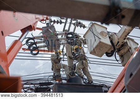 Electricity Workers Climb Poles And Use Electric Cable Cars To Maintain High Voltage Lines On Danger
