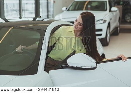 Beautiful Long Haired Woman Getting In A New Car At The Dealership. Attractive Female Customer Exami