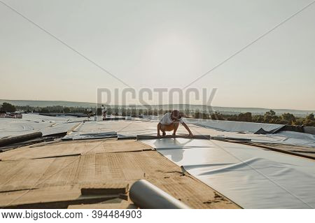 Worker Applies Pvc Synthetic Membrane Roller On Roof Very Carefully.