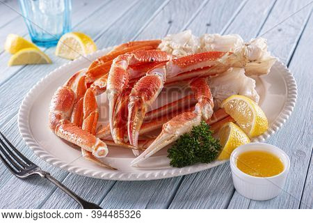 A Plate Of Delicious Snow Crab Leg Clusters With Lemon, Parsley And Melted Butter.