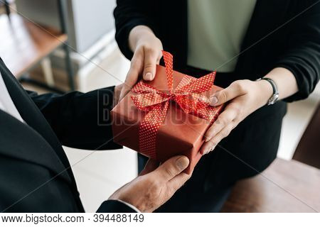Close-up View Of Hands Of Unrecognizable Woman Giving Red Gift Box Tied To Bow Handed To Man. Giving