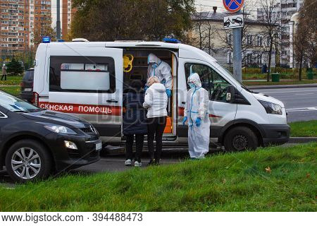 MOSCOW, RUSSIA – October 26 2020: Ambulance at the parking lot. Doctors are wearing protective suits against the coronavirus covid-19 . One woman is helping the other to get into the van. Translation: Ambulance