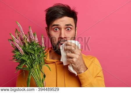 Photo Of Shocked Young Man Allergic To Spring Flowers Or Plants, Has Asthmatic Disease, Redness Arou