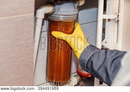 Water Filtration - The Plumber Changes The Dirty Water Filter. Cleaning Of Tap Water.