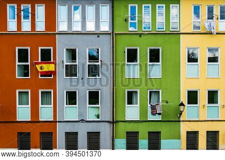 Gijon, Asturias, Spain - October 10, 2020: Colorful Facades With Spanish Flag Hanging From One Of Th