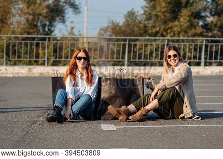 Young Women With Shopping Bags Sitting On Parking