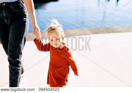 Cute 2-year Old Girl Is Holding Her Mothers Hand During A Walk By The Sea