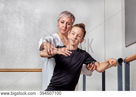 A Beautiful Woman Teaches A Young Man Ballet Near Barre. Graceful Dance.