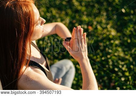 Close-up View Of Red-haired Young Woman With Closed Eyes Holding Hands In Namaste Mudra Pose In Even