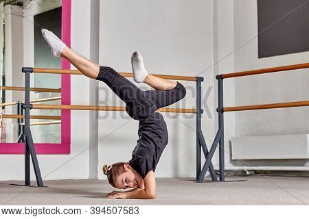 A Young Man Stands On His Head, Legs Apart In A Ballet School On The Carpet.