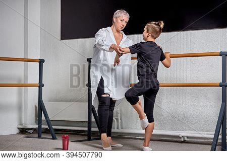 A Young Beautiful Woman In Full Growth Teaches A Man Ballet. Ballet School.