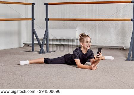 A Young Man Is Sitting On The Splits In The Gym And Holding A Smartphone.