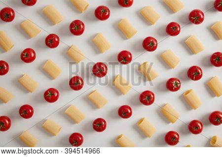 Organic Rigatoni Pasta And Red Cherry Tomatoes Arranged In Rows On White Studio Background. Creative