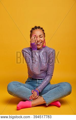 Indoor Shot Of Cheerful Female Keeps Palm On Face, Laughs And Feels Joyful, Sits Crossed Legs, Dress