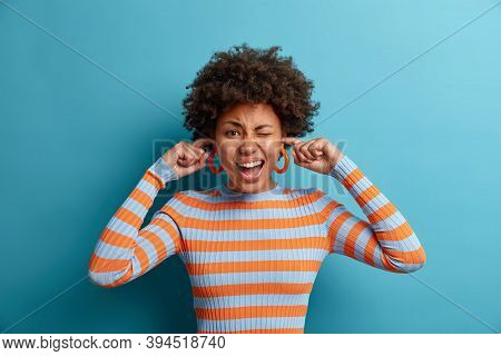 Stressed Emotional Curly Young Woman Plugs Ears And Shouts Loudly, Avoids Noise, Stands Bothered By