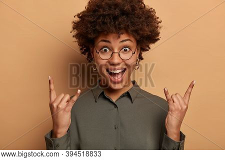 Optimistic Curly Woman Has Joyful Expression, Makes Rock N Roll Gesture, Listens Favourite Music, En
