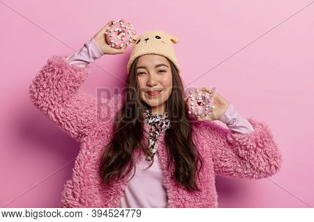 Good Looking Asian Woman Happy To Forget About Diet, Eats Sugary Unhealthy Food, Holds Donuts In Han