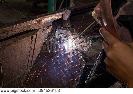 Welding Spark Of Car Mudguard From Welder In Car Repair Shop In Zoom View
