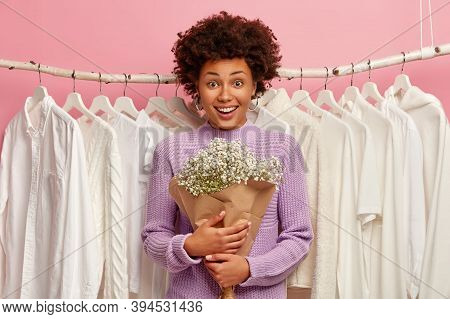 Joyful Dark Skinned Woman Poses In Dressing Room With Bouquet, Wears Purple Sweater, White Clothes O