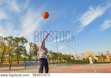 The Young Athlete Threw A Basketball Into The Ring. Sports Activities On The Playground