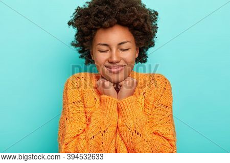 Portrait Of Curly Woman With Crisp Hair, Keeps Hands Under Chin, Feels Pleasure From Hearing Heartwa