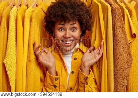 Happy Afro Woman With Toothy Smile, Raises Palms And Shows Big Variety Of Clothes In Store, Looks Th